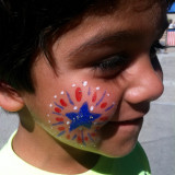 Little boy got his face painted at a 4th of July festival.