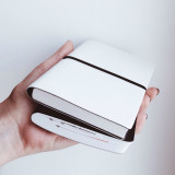 black and white notebooks in the hand