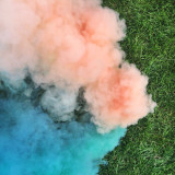Blue and peach smoke bombs on green grass.