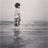 Boy standing in the surf