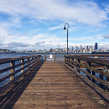 Wooden pier with cityscape in background
