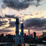 The burning skies above the NYC skyline, two chimneys spewing out clouds