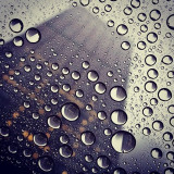 Very artistic shot of the water droplets focused with a building towering