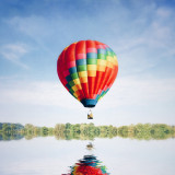Colourful hot air balloon reflected in lake