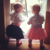 Twins wearing tutus looking outside