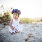Happy little Londyn in her white beach outfit and purple flower crown.