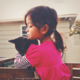 Girl in ponytail holding her cat