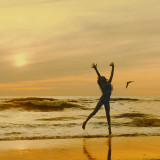 Golden sunset and jumping girl at the beach
