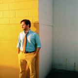 A man in a tie and yellow pants leans against a yellow brick wall.