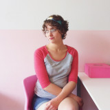 A woman sits in a sunlit bakery on a pink chair,  near a pink cupcake box, against a pink wall, wearing a pink and grey shirt.