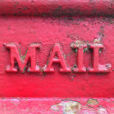 Detail of old moss-covered red mailbox.