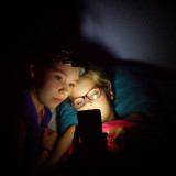 Just before going to sleep, sisters watching a youtube movie