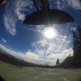 Fisheye view of the sun in the center of a basketball hoop.