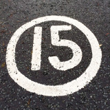 Number 15 painted in white on black road surface