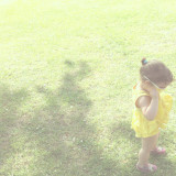 Little girl with yellow dress on grass background
