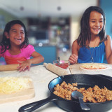 Happy girls making pizza