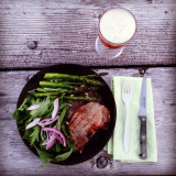 Camp meal of pork chops, salad, asparagus and a cold beer.