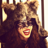 Young woman wearing eye mask, fur hood and red lipstick laughing.