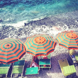 Three beach umbrellas in a row bright orange and green