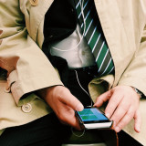 Businessman texting and listening to music