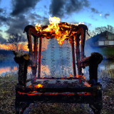 This is a photo of a wing back chair that was set on fire then placed in front of a pond during sunset. At a farm in Ontario Canada