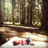 Boy lying down in woods