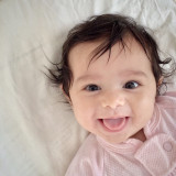 Cute baby girl mischievously smiling.