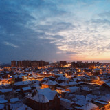 Sunset over the snow-covered roofs