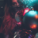 Girl with pink hair behind a Christmas tree.