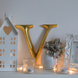 A gold 'V' on a mantel with ornaments and fairy lights