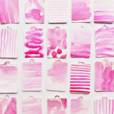 Hand-painted pink paper gift tags arranged neatly on a white background.