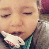 Adorable baby girl sleeping with soother in mouth