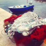 Fishing net in port with small boat in background