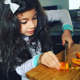 Child cutting a sweet pepper with a chef knife