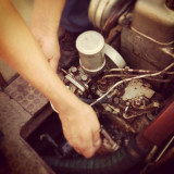 Man repairing old rusty diesel boat engine
