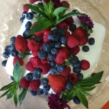 Sponge cake with lemon icing, berries, mint and flowers, taken from above.