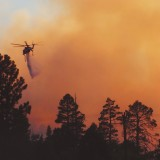 A helicopter dumps water on a forest fire.