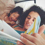 Mother reading to her daughter in bed.