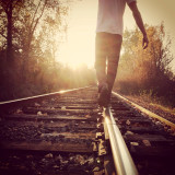 Walking on train tracks into a golden sunset.