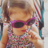 Little girl with sunglasses licking lollipop