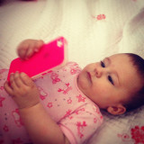 Little baby girl playing with smartphone