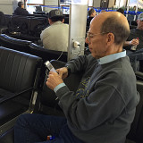 A man using his cellphone while charging it at the airport