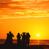 Group of people using cell phones to capture the sunset.
