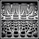 Test Patterns. Another Day in the Lab. A black and white abstract photo of sample tubes in a rack with refracted patterns