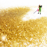 Tiny man with leaf blower scattering gold glitter on a white background.