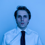 Man in office white shirt and tie looks like American Psycho, blue light