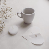 White on white. A cup of coffee, a candle and a paper heart
