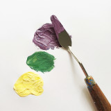Yellow paint, green paint, purple paint and a palette knife on a white background.