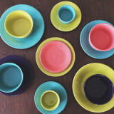 Looking down at colorful Fiestaware dishes on a brown wooden table.