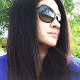 Woman outdoors with long dark hair wearing sunglasses and looking away from camera.